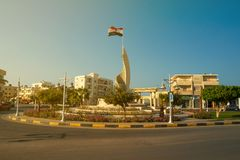 Egypt flag waving. Hurghada, Egypt - November 10, 2018: Street scene with Egypt flag waving in the wind on the square opposite the mosque royalty free stock photos