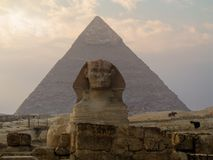 Egypt. Giza valley. Sphinx, and pyramid on the background. The sun and cloudy on the sky Stock Image