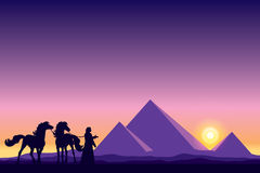 Egypt Great Pyramids with Bedouin and horses silhouettes on suns Stock Photography