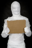 Egypt mummy and cardboard tablet. Egypt mummy hold cardboard tablet on hands royalty free stock photography