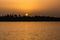 Free Egypt Nile River View At Sunset With Tropical Palm Tree Silhouette And Distant Colorful Sun Going Down Stock Images - 135311844