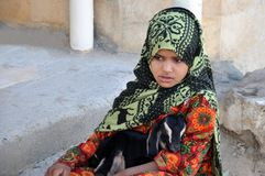 Egypt, October 22, 2012: A girl sits in a bright dress in a hijab with a baby goat in her arms royalty free stock photography