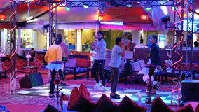 Egyptian mans dance for tourists in the street restaurant at Naama Bay. Egypt, Sharm El Sheikh, April 8, 2019: Egyptian mans dance for tourists in the street stock video