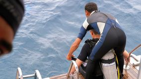 Scuba Divers getting ready to jump off the boat into the Red sea stock footage