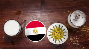 Egypt Vs. Uruguay coasters at the bar with beer pints. royalty free stock photo