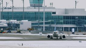 EgyptAir plane landed on Munich Airport MUC. Egyptair aircrafts doing taxi in Munchen Airport, Germany, winter time with snow on runway stock footage