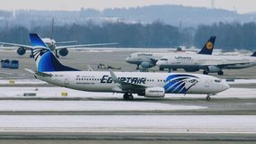 EgyptAir plane landed on Munich Airport MUC. Egyptair aircrafts doing taxi in Munchen Airport, Germany, winter time with snow on runway stock video