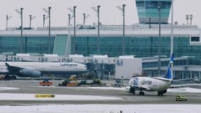 EgyptAir plane landing in Munich Airport MUC. Egyptair aircrafts doing taxi in Munchen Airport, Germany, winter time with snow on runway stock video