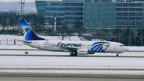 EgyptAir plane taking off from Munich Airport MUC. Egyptair aircrafts doing taxi in Munchen Airport, Germany, winter time with snow on runway stock video