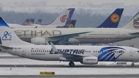 EgyptAir Boeing 737-800 SU-GEH in Munich Airport, MUC. EgyptAir doing taxi on Munich Airport, MUC, snow on runway stock video