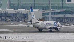 EgyptAir Boeing 737-800 SU-GEH taxiing in Munich Airport, MUC. EgyptAir doing taxi in Munich Airport, MUC, snow on runway stock video