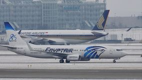 EgyptAir Boeing 737-800 SU-GEH taxiing in Munich Airport, MUC. EgyptAir doing taxi in Munich Airport, MUC, snow on runway stock footage