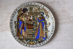 Egyptian antiquarian porcelain plate is made in national style. Egyptians in colourful national clothes are drawn on a plate royalty free stock photo