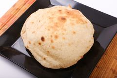 Egyptian bread. On black dish on wooden table royalty free stock photos
