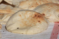 Egyptian bread pita. Egyptian bread piled up on a street seller's cart with a fly sitting on it Stock Photography