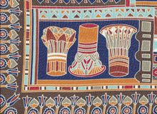 Egyptian capitals. Abstract Egyptian capitals, big tops on silk scarf in blue and copper colors royalty free stock photography