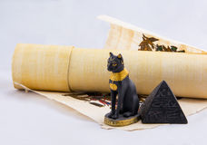 Egyptian cat, a pyramid and papyrus from travels. Egyptian cat, a pyramid and papyrus - souvenirs from travels. Objects from a trip to Egypt Royalty Free Stock Photography