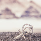 Egyptian Cross Ankh. The Egyptian ankh is a cross in the sand against the backdrop of the Great Pyramids. Photo toned Stock Images
