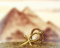 Egyptian Cross Ankh. The Egyptian ankh is a cross in the sand against the backdrop of the Great Pyramids. Photo toned Stock Photo