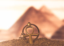 Egyptian Cross Ankh. The Egyptian ankh is a cross in the sand against the backdrop of the Great Pyramids. Photo toned Stock Photos