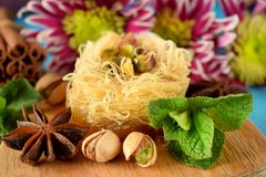 Egyptian dessert Kunafa. Made of kataifi dough with pistachios surrounded by spices, flowers and nuts Royalty Free Stock Image