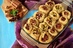 Egyptian dessert Kunafa made of kataifi dough with pistachio and pecan nuts. In a glass baking dish. Top view Stock Images