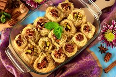 Egyptian dessert Kunafa made of kataifi dough with pistachio and pecan nuts. In a glass baking dish. Top view Royalty Free Stock Images