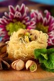 Egyptian dessert Kunafa made of kataifi dough with pistachios. Surrounded by spices, flowers and nuts Stock Photography