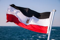 Egyptian Flag Floating in the Sun with Red Sea in the Background stock photo