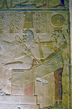 Egyptian Goddess Mut with Pharoah Seti. An ancient egyptian hieroglyphic painted sculpture showing the vulture goddess Mut embracing the Pharoah Seti.  Carving Stock Photo