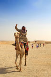Egyptian guide offering to tourists camel ride. GIZA, EGYPT - MARCH 11: Unidentified Egyptian guide offering to tourists camel ride under Great pyramids of Giza Stock Images