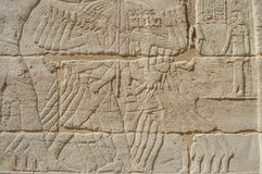 Egyptian hieroglyphic carvings on wall Stock Photos