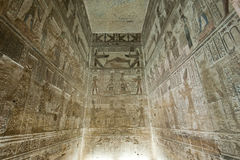 Egyptian hieroglyphic paintings on a temple wall. Hieroglyphic carvings and paintings on the interior walls of an ancient egyptian temple Royalty Free Stock Image