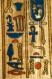 Egyptian hieroglyphics on papyrus. Close up of Egyptian hieroglyphics on ancient  papyrus painting on golden Stock Image