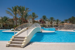 Egyptian hotel swimming pool. With bridge and palms stock photo
