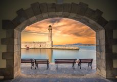 The Egyptian lighthouse at the old harbor of Rethimno through a frame of an arched door, Crete. Stock Images