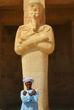 Egyptian man folding arms in front of statue Stock Photos