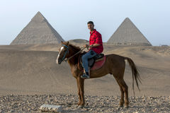 An Egyptian man sits on his horse in front of The Pyramid of Khafre and the Pyramid of Khufu in Giza in Cairo, Egypt. Royalty Free Stock Images