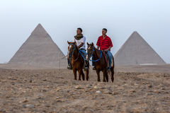 Egyptian men sit on their horses infront of The Pyramid of Khafre and the Pyramid of Khufu in Egypt. Royalty Free Stock Images