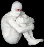 Egyptian mummy emo. Sitting on the black background Royalty Free Stock Image