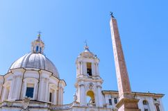 The Egyptian Obelisk in Piazza Navona, Rome, with the dome and b stock photo