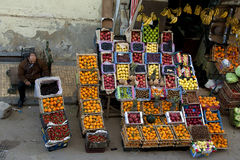 Egyptian peddler sat beside a curbside fruit shop Royalty Free Stock Photos
