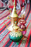 Egyptian perfume bottles. Arranged on a hand-woven Omani rug. A copper replica of an old coffee pot is faded in the background stock photography
