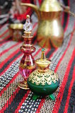 Egyptian perfume bottles. Arranged on a hand-woven Omani rug. A copper replica of a traditional coffee pot and small cup is faded in the background stock photography