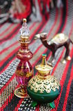 Egyptian perfume bottles. Arranged on a hand-woven Omani rug. A small copper replica of a camel is faded in the background stock photo