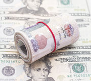 Egyptian Pounds Roll on US Dollars. Egyptian Pounds Roll with Red Thread on US Dollars Royalty Free Stock Images
