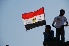 Egyptian Revolution - January 25. Egyptian flag waving in the hand of a young man on top of a tall column in Tahrir Square. Shot on July 7th 2011, one of many Stock Photo