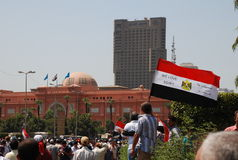 The Egyptian Revolution - We love Egypt. A man holding an Egyptian flag with the phrase We Love Egypt. In Tahrir square with the Egyptian museum in the Stock Image