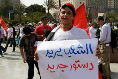 Egyptian Revolution - People Demand. A young man in Tahrir (Liberation) square holding a sign that says People Demand a new Constitution. Taken on Friday, April Royalty Free Stock Photography