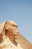 Egyptian sphinx. Pyramid, blue sky and flying airplain Royalty Free Stock Images